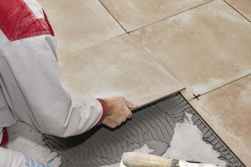 Home improvement, renovation - handyman laying tile with level royalty free stock photo