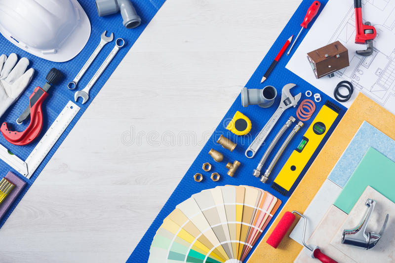 Home improvement and repair work table. Home improvement and repair concept, plumbing work tools, tap, tiles and color swatches top view royalty free stock images