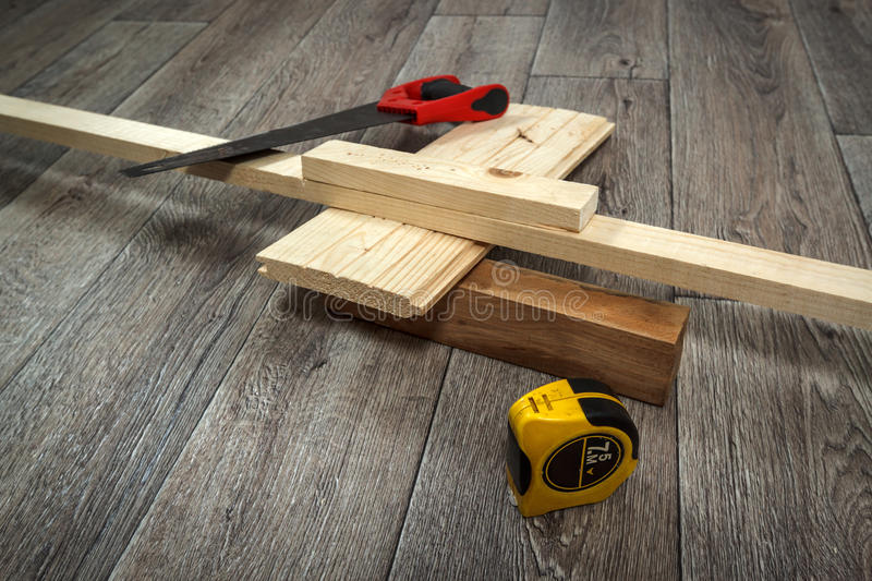 Home improvement, saw, timber and ruler on wooden floor. Home improvement process, saw, timber and ruler on wooden floor, horizontal view stock image