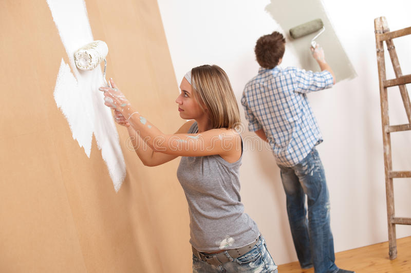 Home improvement: Young couple painting wall. With paint roller stock image