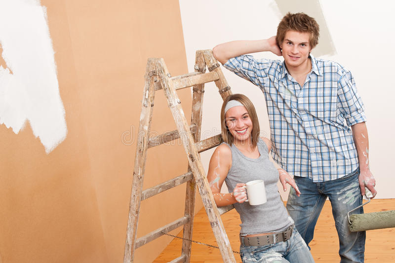 Home improvement: Young couple painting wall. With paint roller stock photography