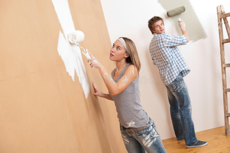 Home improvement: Young couple painting wall. With paint roller royalty free stock photos