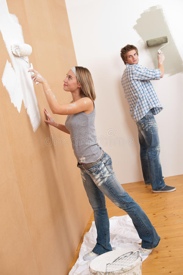Home improvement: Young couple painting wall. With paint roller royalty free stock photo