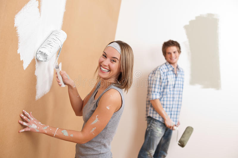 Home improvement: Young couple painting wall stock images