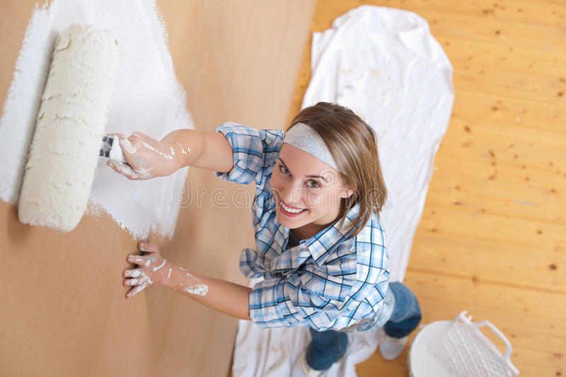 Home improvement: Young woman painting wall. With paint roller stock photo
