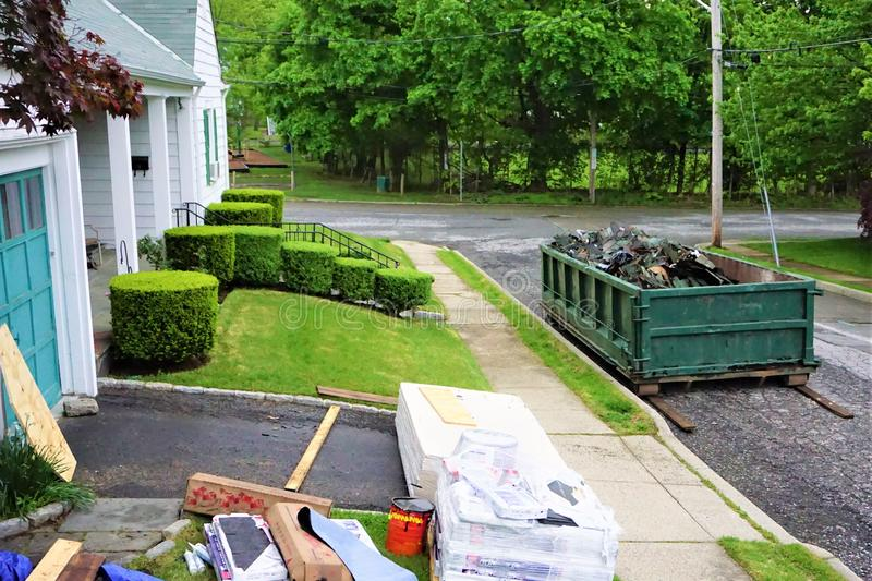 Home improvements roofing do it yourself. Old tar roofing tiles tossed in metal dumpster on street, new packaged roof tiles unopened and equipment sit next to royalty free stock image