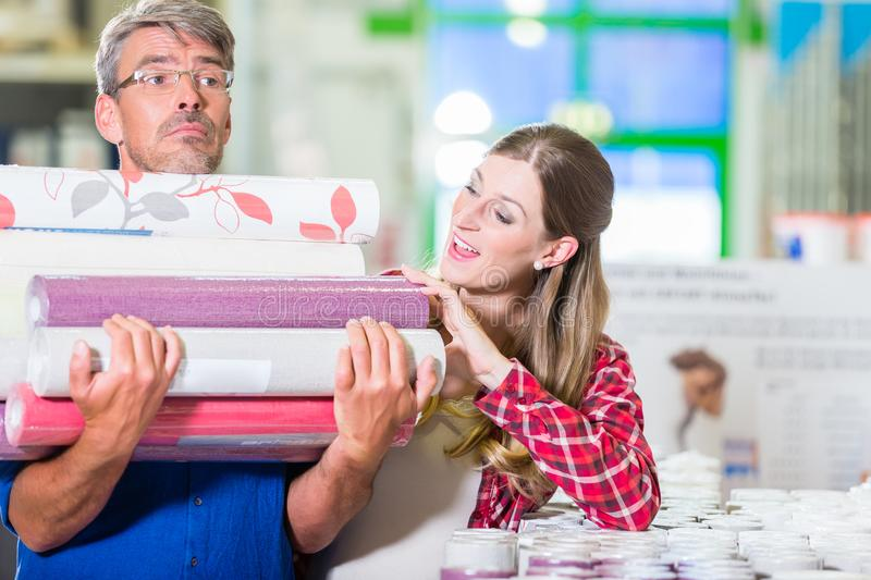 Home improving couple buying wallpapers at hardware store. Home improving couple, women and man, buying many rolls of wallpapers at hardware store for do-it royalty free stock images