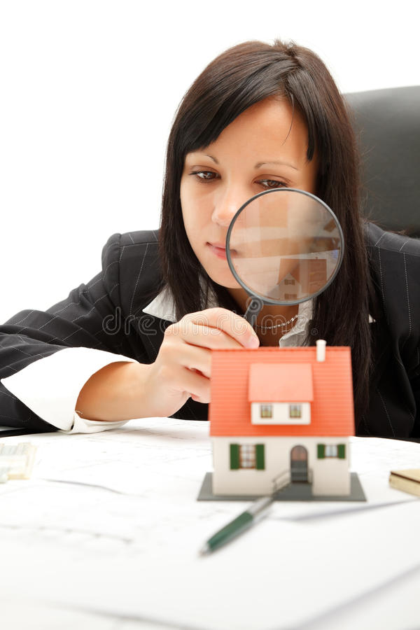 Home inspection. Attractive young business woman inspects a home with magnifying glass stock photography