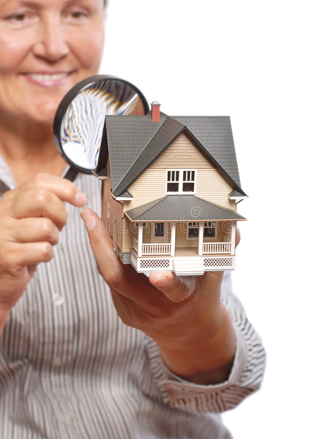 Home inspection. Senior woman inspecting a home with a magnifying glass royalty free stock photography