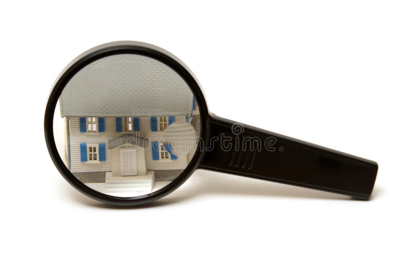 Home Inspection Concept. A home inspection concept using a model house and a magnifying glass stock photography