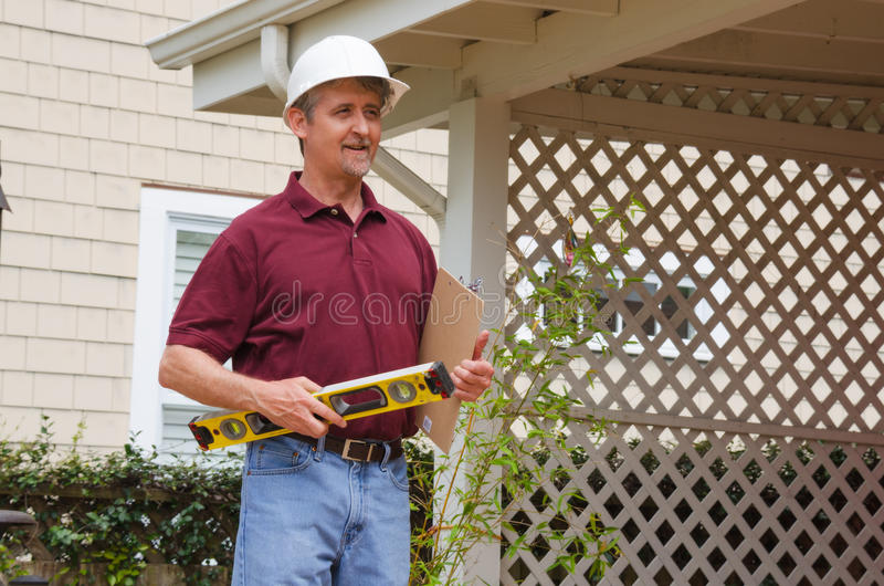 Home inspector house building contractor. A smiling home inspector or house building repair contractor in a hard hat holding a level and a clipboard outside a stock image
