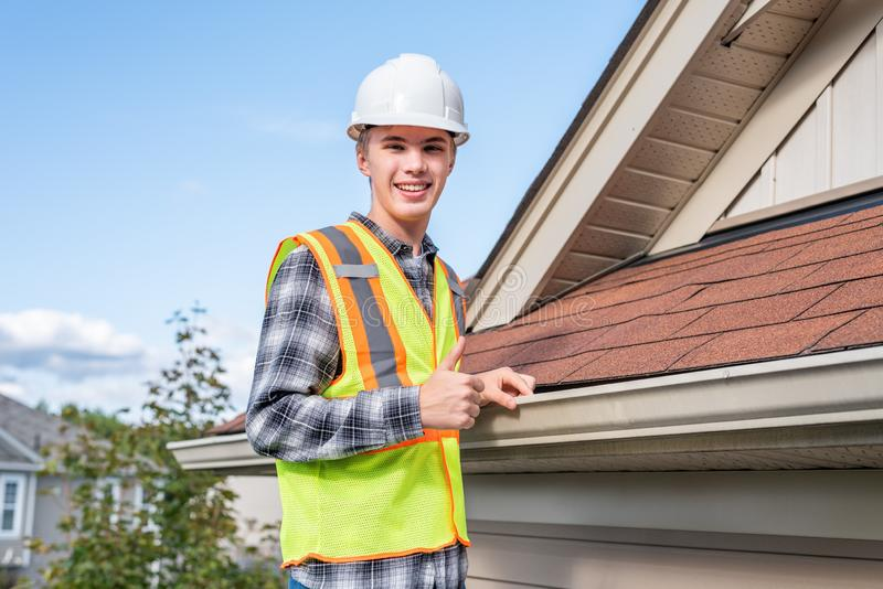 Home inspector providing an inspection to a house. The image displays a home inspector standing on a ladder and providing an inspection to the roof of a house royalty free stock photography