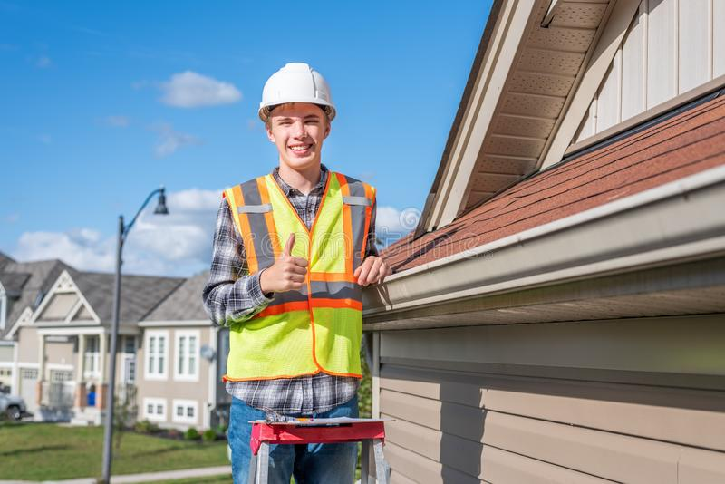 Home inspector providing an inspection to a house. The image displays a home inspector standing on a ladder and providing an inspection to the roof of a house royalty free stock images