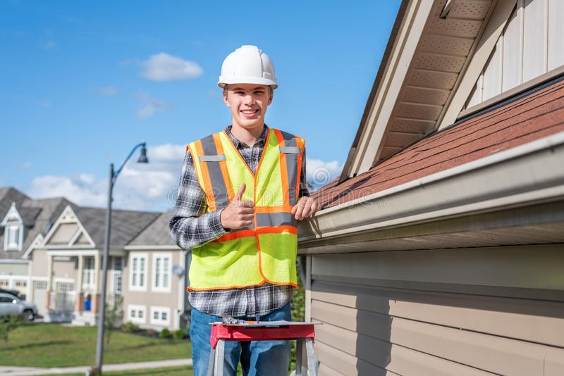 Home inspector providing an inspection to a house. The image displays a home inspector standing on a ladder and providing an inspection to the roof of a house royalty free stock photos