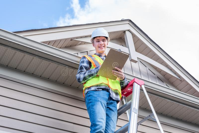 Home inspector providing an inspection to a house. The image displays a home inspector standing on a ladder and providing an inspection to the roof of a house stock image