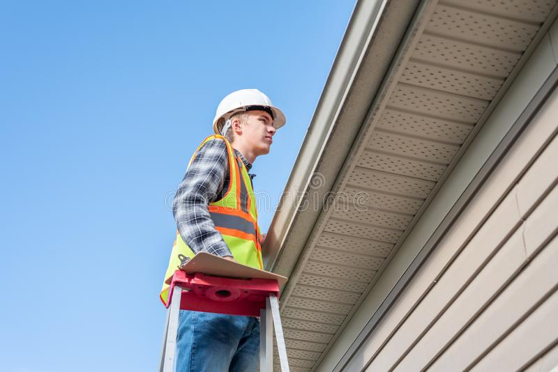 Home inspector providing an inspection to a house. The image displays a home inspector standing on a ladder and providing an inspection to the roof of a house stock photography