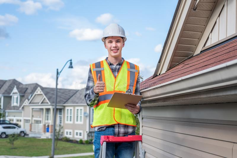 Home inspector providing an inspection to a house. The image displays a home inspector standing on a ladder and providing an inspection to the roof of a house royalty free stock image