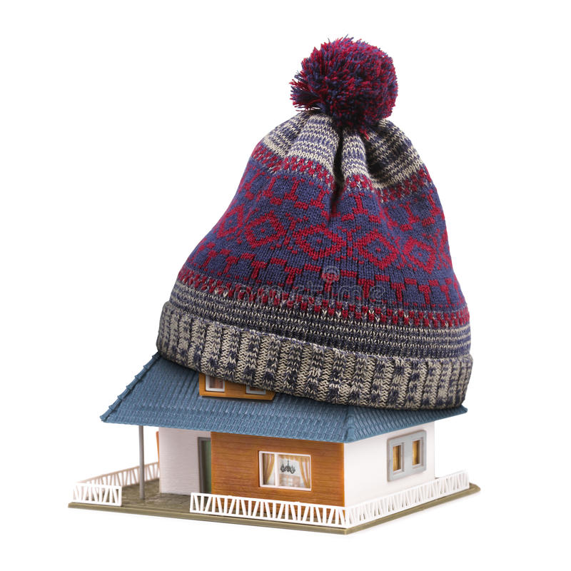 Home insulation or insurance concept. hat on house roof isolated. Home insulation or insurance concept. winter hat on house roof isolated on white stock images