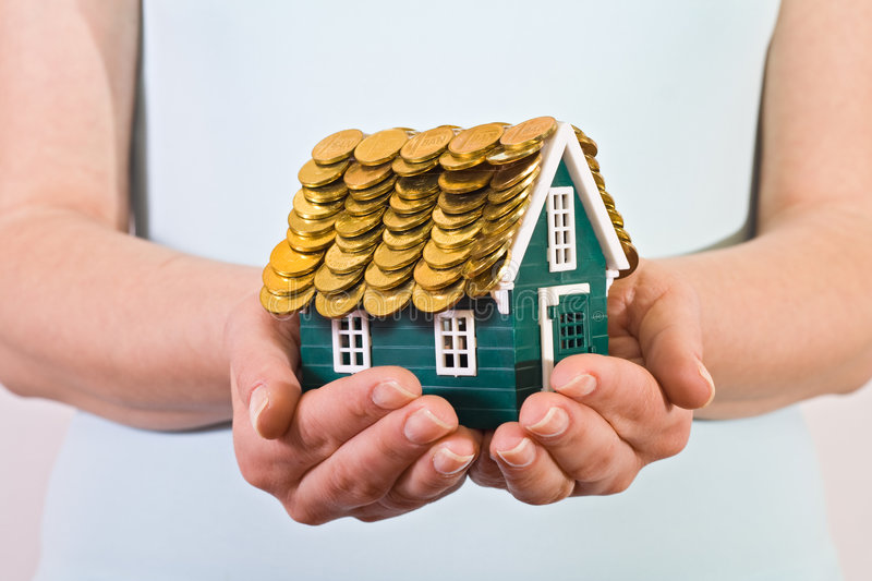Home insurance concept. House with coins roof- home insurance concept royalty free stock photo