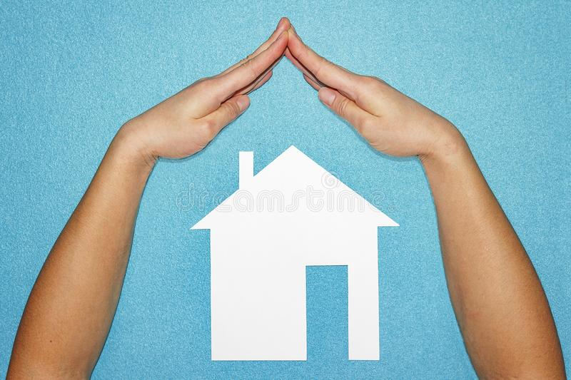 Home insurance concept. Hands in form of roof over house of white paper on blue background.  stock images