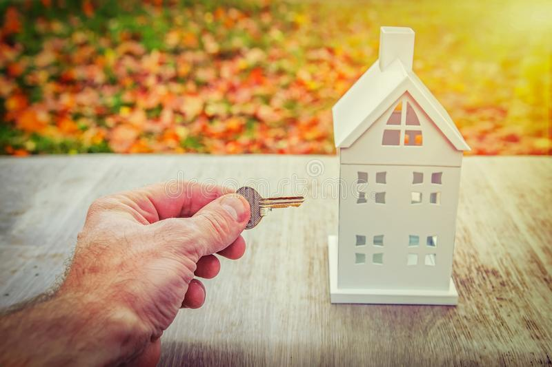Home insurance concept. key of house in hand of man near miniature house model against background of green park in sunny day royalty free stock photos