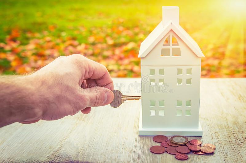 Home insurance concept. Safety of family and home. key in hand closes miniature house with money coins. Save property in house stock photos