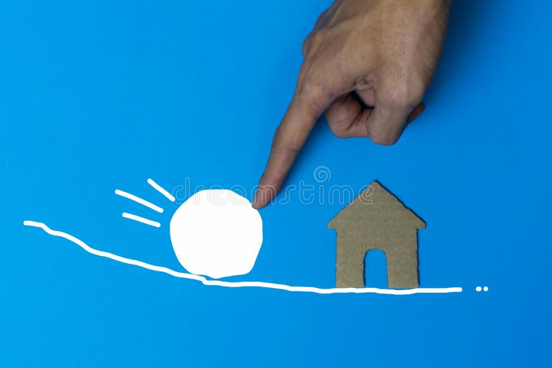 Home insurance concepts. A businessman using hand holding or protect a small house model from a white stone on blue background. Property safety. Real estate stock photography