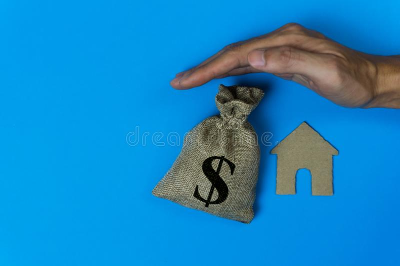Home insurance concepts. House protect. A man hand protected a small house and money bag over a roof on blue background.  stock photography