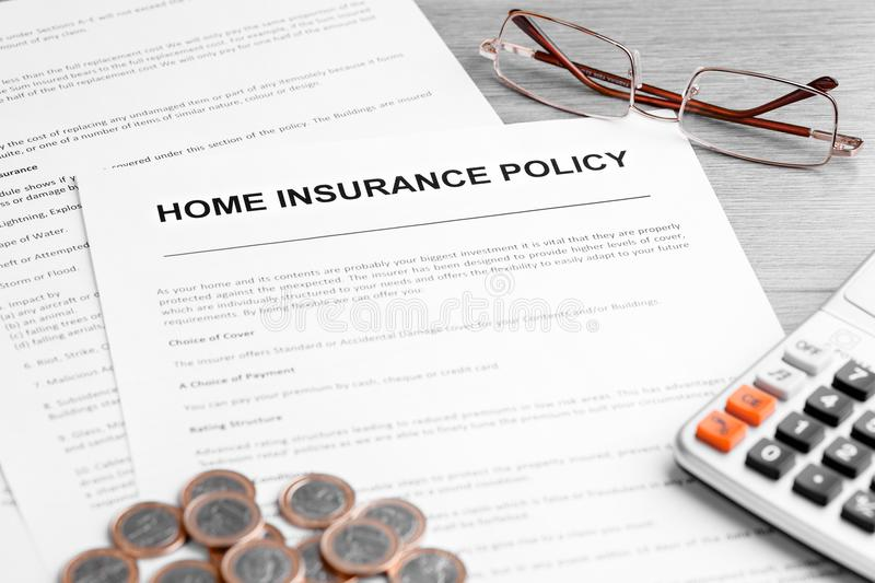 Home Insurance Policy. Calculator, Glasses and Euro Coins on Table. Home insurance policy. Calculator, glasses, documents and euro coins on table. Business and stock photo