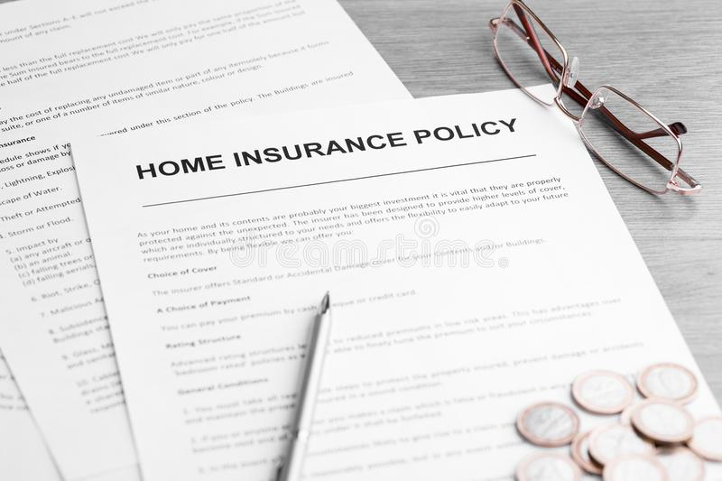 Home Insurance Policy. Pen, Glasses and Coins on a Table. Home insurance policy. Glasses, documents, pen and coins on a table. Business and insurance background stock photos