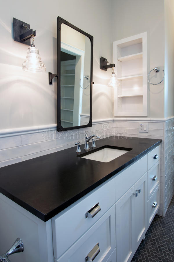 Home interior bathroom mirror and sink. Bathroom mirror, sink, tile floor, and white hardwood cabinets of modern new cottage style home royalty free stock photo