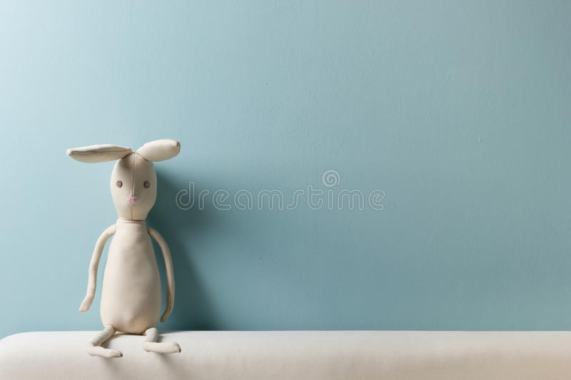 Home interior. Childhood. Blue background. Toy sitting on a couch. Copy space. Home interior. Childhood. Blue background. Toy sitting on a couch. Copy space stock photos