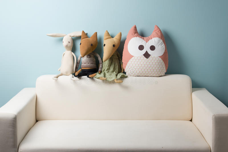 Home interior. Childhood. Blue background. Toy sitting on a couch. Copy space. Home interior. Childhood. Blue background. Toy sitting on a couch. Copy space royalty free stock images