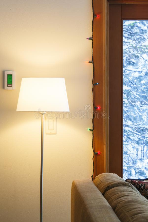 Home interior living room in winter with digital electronic thermostat, floor lamp and view through windows of snowy outdoors royalty free stock images