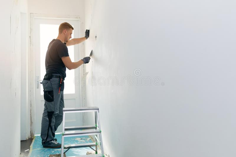 Home interior construction - worker repairing wall royalty free stock photos