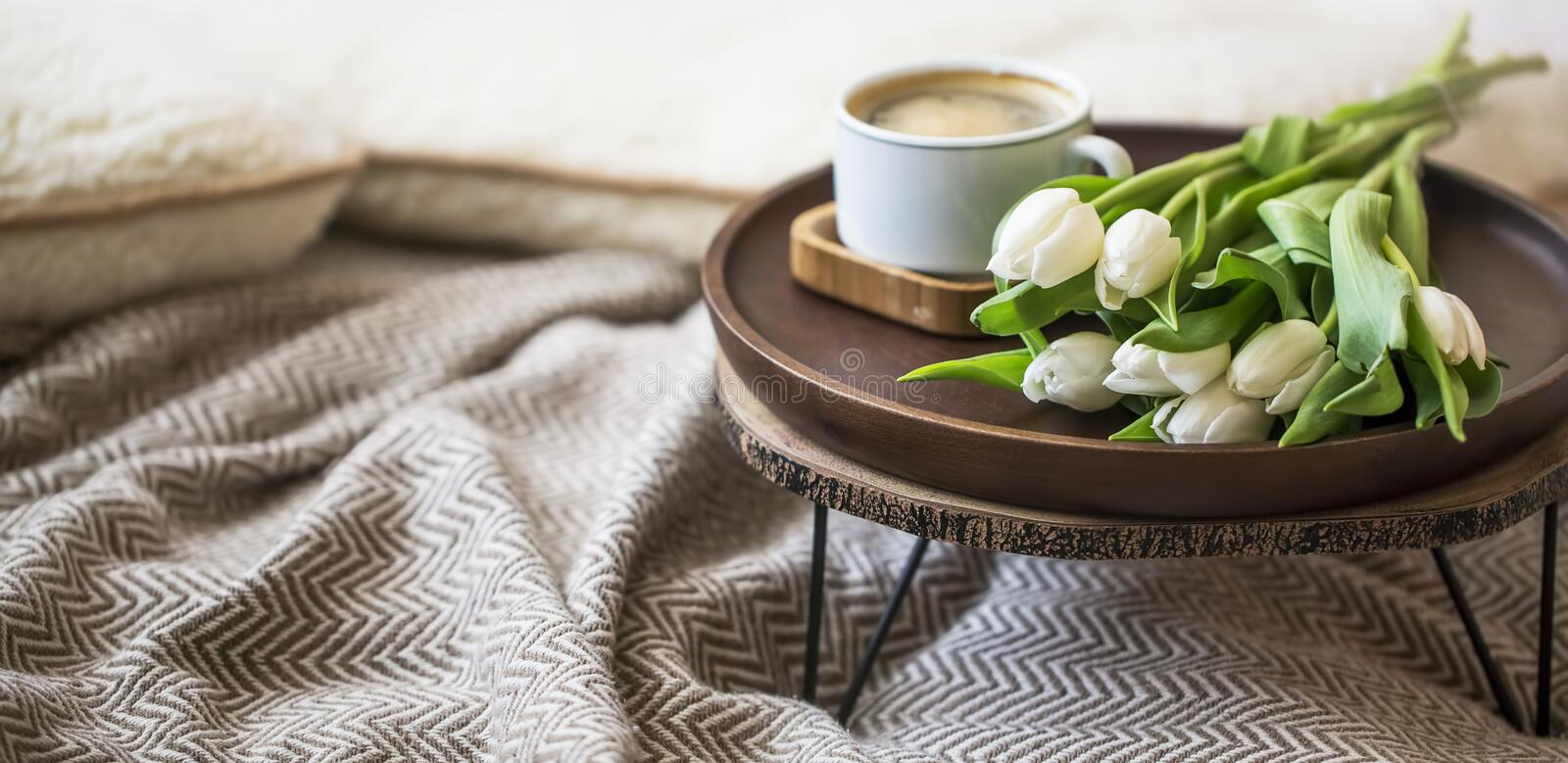 Home interior decor with wooden table, tulips flowers bouquet and coffee cup, cozy blanket, spring interior lifestyle decorations royalty free stock photography