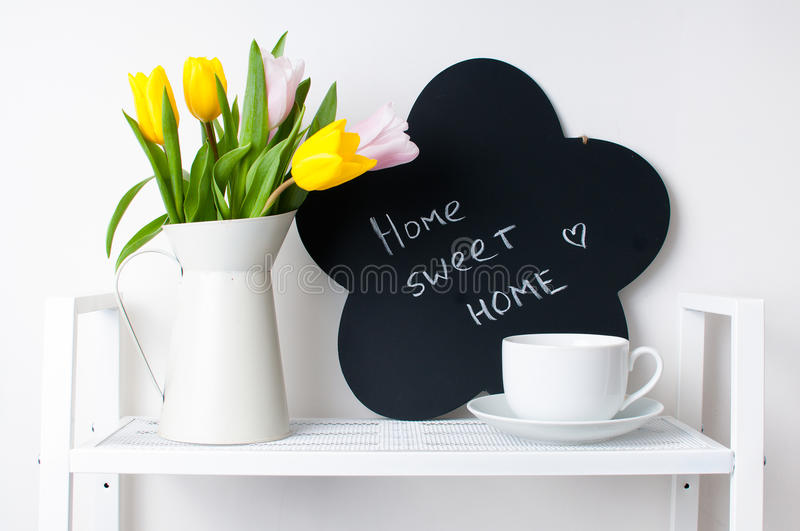 Home interior decoration: a bouquet of tulips, a cup and a chal. Home interior decoration: a bouquet of tulips in a jug, cup and saucer, and chalk board on the