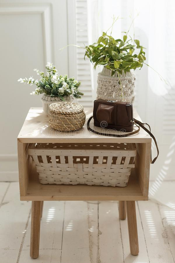 Home interior decoration with green small plant pots, basket and photocamera case on a table. Cozy interior concept. Home interior decoration with green small royalty free stock images