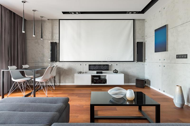 Home interior with projector scree. Elegant home interior with projector screen, table, chairs and cabinet royalty free stock images