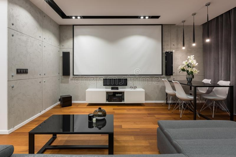 Home interior with projector screen. Modern table and white chairs royalty free stock image