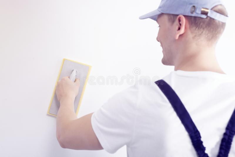 Home interior renovation handyman smoothing down a white wall wi. Th a sandpaper tool stock photo