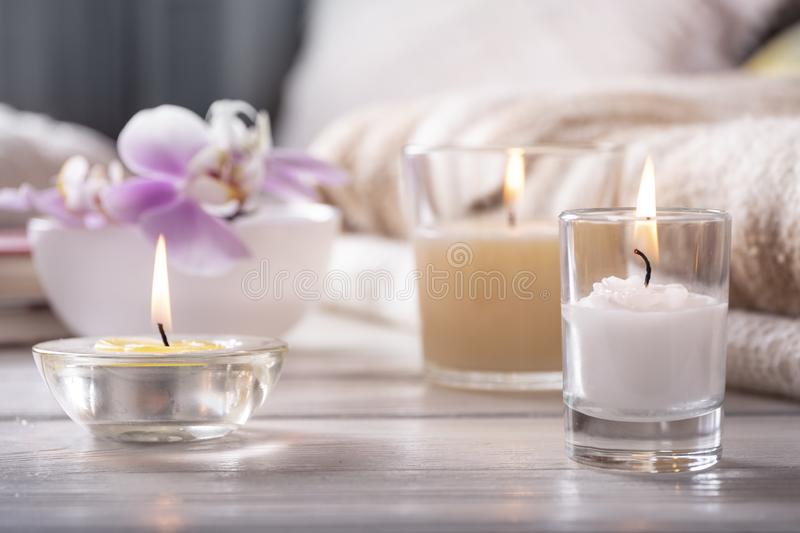 Home interior. Still life with detailes. Flower is vase, candles, on white wooden table, the concept of coziness stock images
