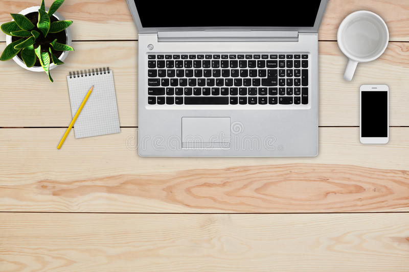 Home interior. Top view of wooden desk with laptop, cell phone, blank notebook for text and pencil, empty white mug and green flow. Er. Desktop of business royalty free stock images