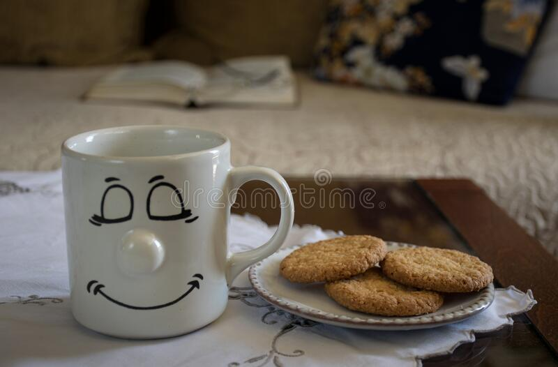 Home interior: a white cup of coffee or tea with cookies on the table and blurred sofa, book and pillow as background. Home interior: a white cup of coffee or royalty free stock photography
