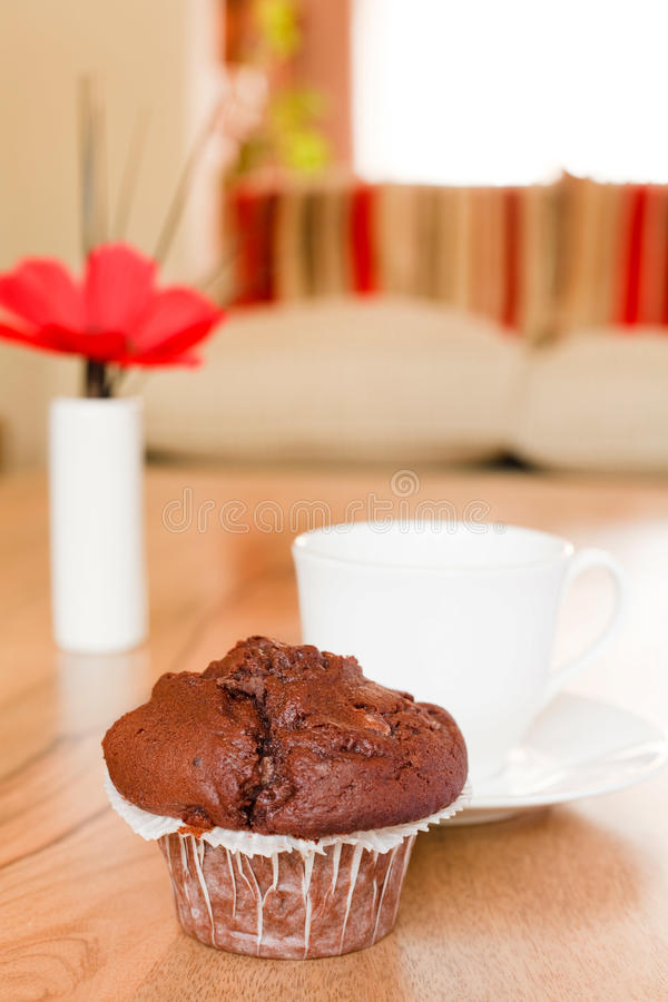 Home interiors. Chocolate muffin on a coffee table in a luxury home interior stock image