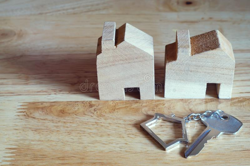 House key with home keyring and wooden home model on bright background, real estate concept, copy space. Home key with home keyring and wooden house model on royalty free stock photography