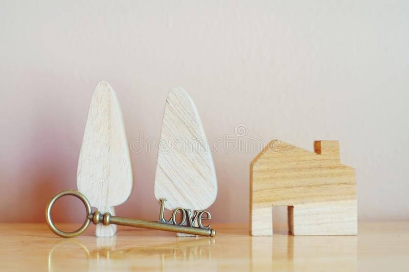 House key with home keyring and wooden home model on bright background, real estate concept, copy space. Home key with home keyring and wooden house model on stock images