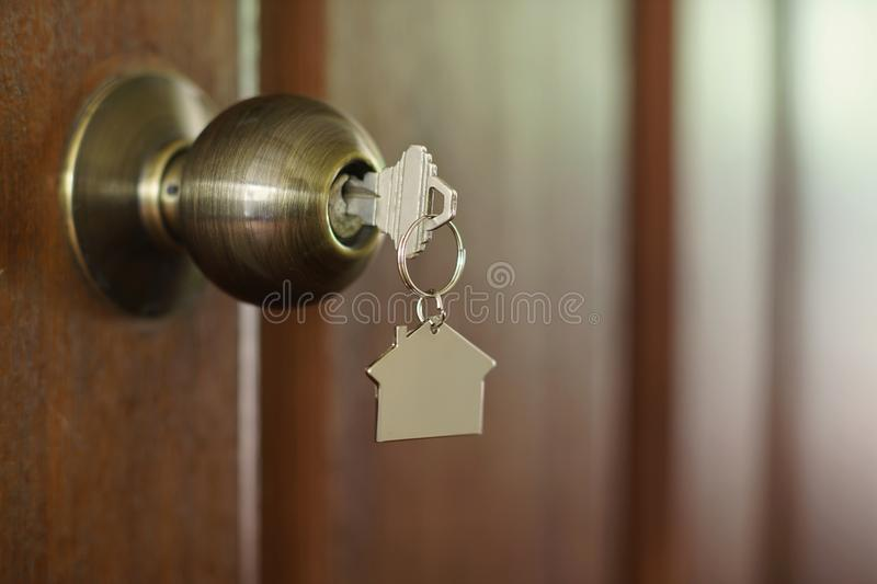 Home key with house keychain in keyhole, property concept. Home key with metal house keychain in keyhole, property concept stock images