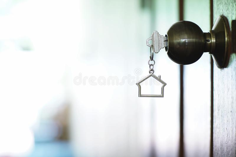 Home key with house keychain in keyhole, property concept. Home key with metal house keychain in keyhole, property concept stock photo