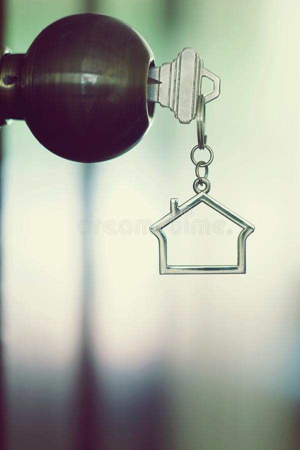 Home key with house keychain in keyhole, property concept. Home key with metal house keychain in keyhole, property concept stock photography